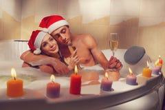 Paret i santa hattar tycker om ett bad arkivbild