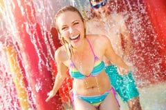 Paret, i swimmning, passar under den plaskande springbrunnen för sommarsun för värme varm ny termometer Royaltyfri Foto