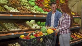 Paret köper grönsaker på gallerian royaltyfri bild