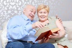 Paret läser en bok hemma Royaltyfri Bild