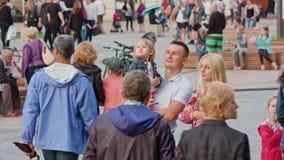 Paret med barnet talar på den Litewski fyrkanten royaltyfria bilder