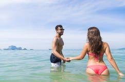 Paret på strandsommarsemester, ungdomari vatten, mankvinnainnehav räcker havshavet Royaltyfri Foto