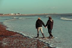 Paret promenerar en UK-strand i vintern Arkivfoton