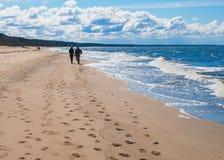 Paret promenerar stranden under blå himmel royaltyfri bild