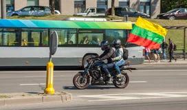 Paret rider en motorcykel med den litauiska flaggan royaltyfri bild