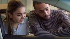 Paret ser inom bilen på återförsäljaren royaltyfri fotografi