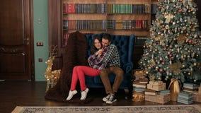 Paret sitter att omfamna nära julgranen hemma arkivfilmer