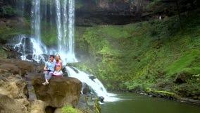 Paret sitter vaggar på grabbkontrollflycam vid vattenfallet lager videofilmer
