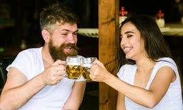 Paret som är förälskat på datum, dricker öl Bästa vän eller vän som dricker i bar Man den skäggiga hipsteren och flickan med ölex royaltyfri foto