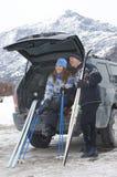 Paret som kopplar av på baksida av bilen med, skidar och Poles Royaltyfria Bilder