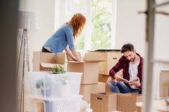 Paret som packar upp material från lådan, boxas medan flyttning-in i nytt hem arkivbild