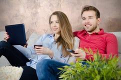 Paret tycker om fri tid och hållande ögonen på tv royaltyfri foto