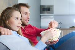 Paret tycker om fri tid och hållande ögonen på tv royaltyfria bilder