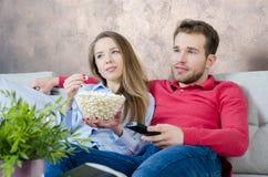 Paret tycker om fri tid och hållande ögonen på tv royaltyfria foton