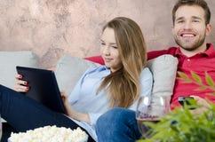 Paret tycker om hållande ögonen på TV för fri tid royaltyfri foto