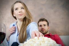 Paret tycker om hållande ögonen på TV för fri tid arkivbilder