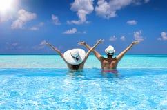 Paret tycker om sikten till havet i en simbassäng royaltyfri fotografi