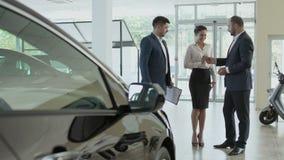 Paret undertecknar avtalet av köpandebilen i bilvisningslokalen och får nyckel- arkivfilmer