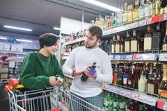 Paret väljer alkohol i supermarket och samtalen maken visar flickan en flaska av vin i supermarket arkivbild