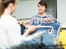 Paret väljer jeans på shoppa Royaltyfri Bild