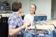 Paret väljer jeans på shoppa Royaltyfri Foto