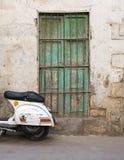 Parete abbandonata con la finestra verde di legno chiusa con la griglia del ferro Fotografie Stock