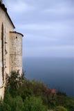 Parete antica con pochi torre e mare che spariscono nel cielo con Fotografia Stock Libera da Diritti