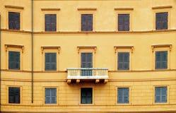 Parete arancio con le finestre ed il balcone fotografie stock