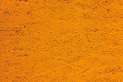 Parete arancio da una facciata esteriore grezza della casa con colore vivo intenso come backgruond rustico vuoto di struttura fotografia stock
