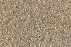 parete beige di struttura del fondo di gesso con le piccole pietre naturali variopinte immagine stock