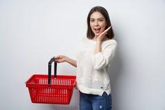 Parete bianca facente una pausa sorpresa della donna castana che tiene cestino della spesa vuoto fotografie stock libere da diritti