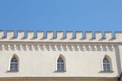 Parete bianca reale del castello con i merli e le finestre gotiche immagini stock