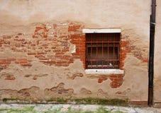 Parete con il mattone esposto e finestra con le barre Fotografie Stock