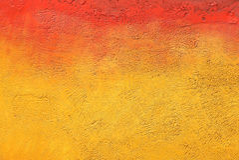 Parete con la pittura giallo arancione variopinta del modello della pittura Fotografia Stock