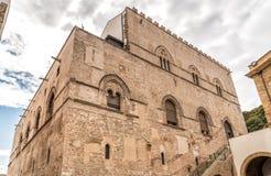 Parete con le finestre munite di montanti con gli intarsi della pietra della lava del palazzo Steri Chiaramonte, Palermo, Sicilia fotografia stock libera da diritti