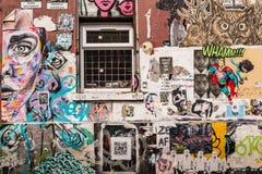 Parete coperta nei murali della carta da parati e dei graffiti Immagine Stock