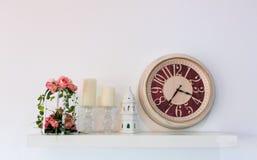 Parete decorata con gli orologi, il fiore e la candela immagine stock