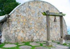 Parete dell'arco della pietra del modello con colonne di legno le vecchie di Rusty Bell Hang By Two immagine stock
