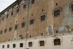 Parete della costruzione della prigione con le finestre delle cellule del pricon con le barre fotografia stock
