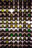 Parete delle bottiglie di vino vuote Le bottiglie di vino vuote impilate-su su una un altro nel modello si sono accese dalla luce immagine stock libera da diritti