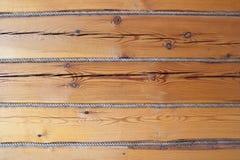 Parete di legno di marrone del ceppo di Horisontal decorata con la corda fotografie stock libere da diritti