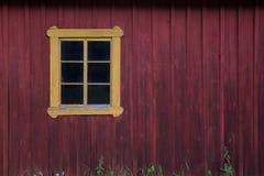 Parete di legno rossa con la finestra gialla Copi lo spazio immagine stock libera da diritti