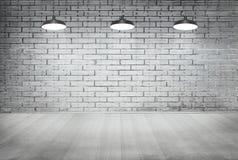 Parete di lerciume del mattone della stanza e pavimento bianchi di legno con la lampada del soffitto Fotografia Stock