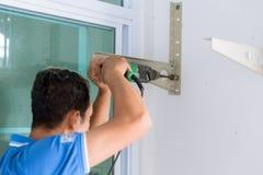 Parete di perforazione del lavoratore per installare il supporto all'aperto del refrigeratore fotografie stock libere da diritti