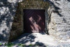 Parete di pietra antica e porta di legno semicircolare medievale fotografia stock
