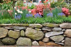 Parete di pietra asciutta e giardino variopinto Immagine Stock