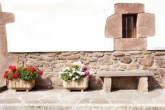 Parete di pietra con il benchon che della pietra del windowand una via ha ornato con i vasi da fiori Immagini Stock Libere da Diritti