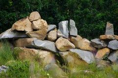 Parete di pietra con il fondo confuso della natura Immagini Stock