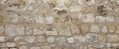 Parete di pietra del vecchio granito con la cucitura del cemento, lavoro in pietra ampio Backgrou Fotografia Stock