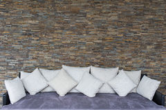 Parete di pietra moderna con il sofà porpora Fotografia Stock Libera da Diritti